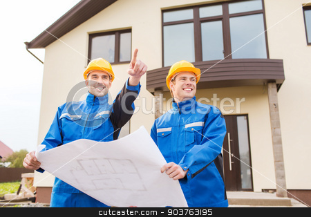 smiling builders with blueprint pointing finger stock photo, building, teamwork and people concept - two smiling builders in hardhats and overalls with blueprint pointing finger in front of house outdoors by Syda Productions