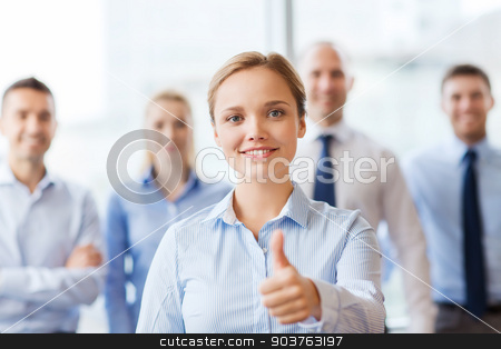 smiling businesswoman showing thumbs up in office stock photo, business, people, gesture and teamwork concept - smiling businesswoman showing thumbs up with group of businesspeople in office by Syda Productions