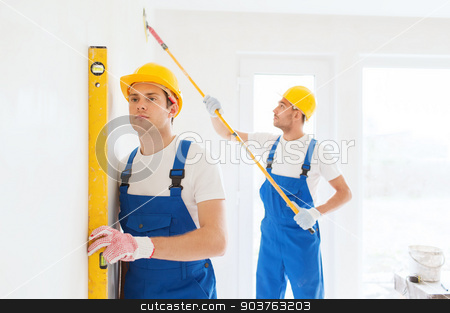group of builders with tools indoors stock photo, building, teamwork and people concept - group of builders in hardhats with tools indoors by Syda Productions