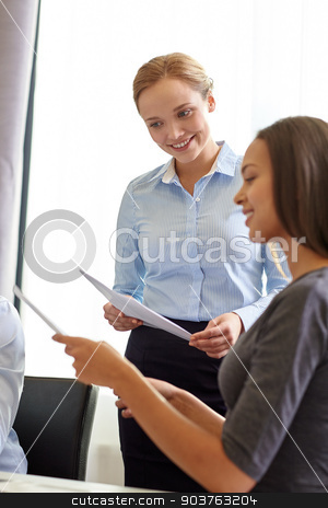 smiling businesswomen with papers in office stock photo, business, people and teamwork concept - smiling businesswomen with papers talking in office by Syda Productions