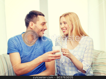 smiling man giving cup of tea or coffee to wife stock photo, love, family, healthy food and happiness concept - smiling man giving cup of tea or coffee to wife or girlfriend at home by Syda Productions