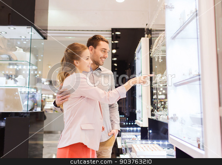 couple looking to shopping window at jewelry store stock photo, sale, consumerism and people concept - happy couple pointing finger to shopping window at jewelry store in mall by Syda Productions