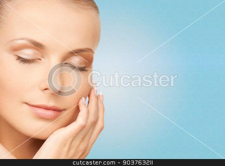 beautiful young woman touching her face stock photo, beauty, people and health concept - beautiful young woman touching her face over blue background by Syda Productions