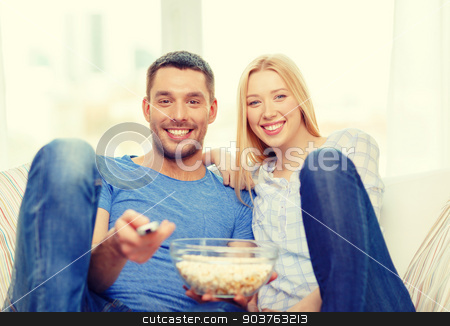 smiling couple with popcorn watching movie at home stock photo, food, love, family and happiness concept - smiling couple with popcorn watching movie at home by Syda Productions