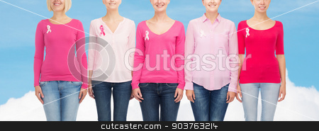 close up of women with cancer awareness ribbons stock photo, healthcare, people and medicine concept - close up of smiling women in blank shirts with pink breast cancer awareness ribbons over blue sky and white cloud background by Syda Productions