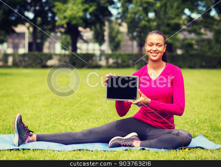smiling woman with tablet pc outdoors stock photo, fitness, park, technology and sport concept - smiling african american woman with tablet pc computer sitting on mat outdoors by Syda Productions