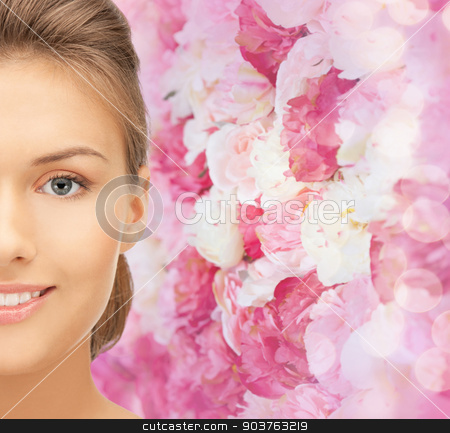 beautiful young woman half face stock photo, beauty, people and health concept - beautiful young woman face over pink floral background by Syda Productions