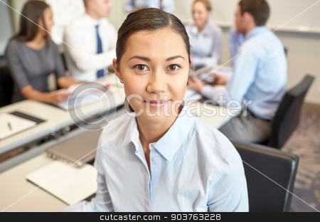 group of smiling businesspeople meeting in office stock photo, business, people and teamwork concept - smiling businesswoman with group of businesspeople meeting in office by Syda Productions