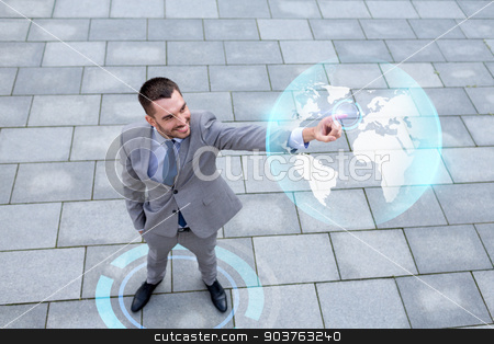 smiling businessman with globe projection outdoors stock photo, global business, development, technology and people and concept - young smiling businessman pointing finger to virtual globe projection outdoors from top by Syda Productions