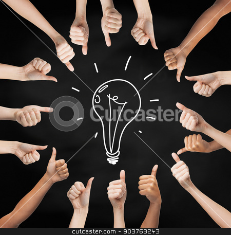 hands showing thumbs up in circle over bulb symbol stock photo, gesture, people, idea and development concept - human hands showing thumbs up in circle over black board background with drawing of lightning bulb in center by Syda Productions