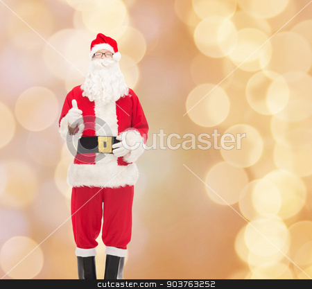 man in costume of santa claus stock photo, christmas, holidays, gesture and people concept- man in costume of santa claus showing thumbs up over beige lights background by Syda Productions