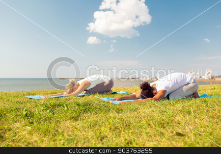 couple making yoga exercises outdoors stock photo, fitness, sport, people and lifestyle concept - couple making yoga exercises on mats outdoors by Syda Productions