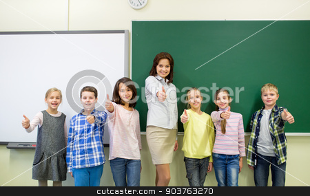 group of school kids and teacher showing thumbs up stock photo, education, elementary, gesture and people concept - group of school kids and teacher showing thumbs up in classroom by Syda Productions