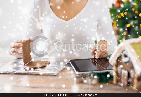 close up of woman making gingerbread houses stock photo, cooking, people, christmas and technology concept - close up of woman with tablet pc computer making gingerbread houses at home by Syda Productions