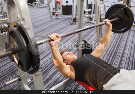 young man flexing muscles with barbell in gym stock photo, sport, bodybuilding, lifestyle and people concept - young man with barbell flexing muscles and making bench press in gym by Syda Productions