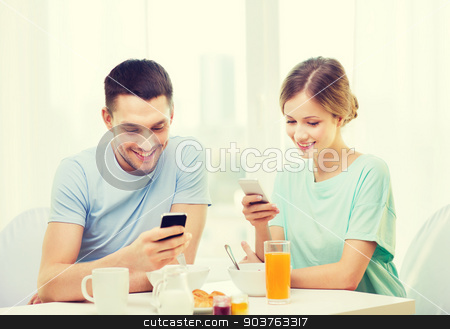 smiling couple with smartphones reading news stock photo, food, home, couple and technology concept - smiling couple with smartphones reading news and having breakfast at home by Syda Productions
