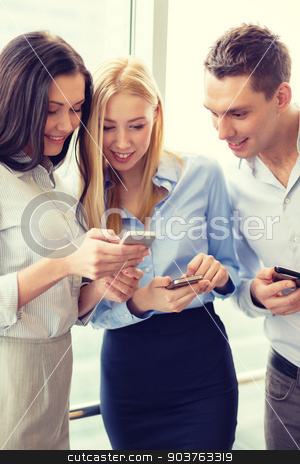 smiling business team with smartphones in office stock photo, business and technology concept - smiling business team with smartphones in office by Syda Productions