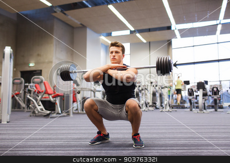 young man flexing muscles with barbell in gym stock photo, sport, bodybuilding, lifestyle and people concept - young man with barbell doing squats in gym by Syda Productions