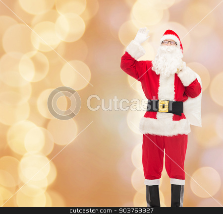 man in costume of santa claus with bag stock photo, christmas, holidays, gesture and people concept - man in costume of santa claus with bag waving hand over beige lights background by Syda Productions