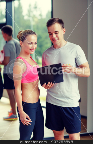 smiling young woman with personal trainer in gym stock photo, fitness, sport, exercising and diet concept - smiling young woman with personal trainer in gym by Syda Productions