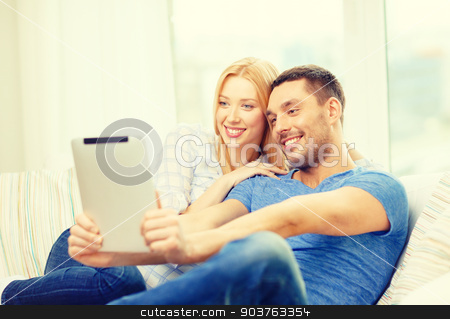 smiling happy couple with tablet pc at home stock photo, love, family, technology, internet and happiness concept - smiling happy couple witl tablet pc computer at home by Syda Productions