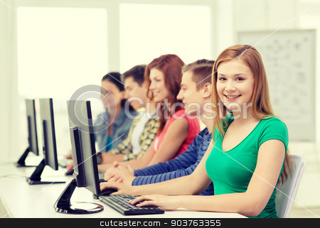 female student with classmates in computer class stock photo, education, technology and school concept - smiling female student with classmates in computer class at school by Syda Productions