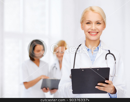 smiling female doctor with clipboard stock photo, healthcare and medicine concept - smiling female doctor with stethoscope and clipboard by Syda Productions