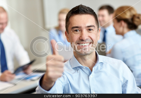 group of smiling businesspeople meeting in office stock photo, business, people, gesture and teamwork concept - smiling businessman showing thumbs up with group of businesspeople meeting in office by Syda Productions