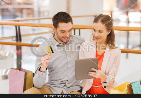couple with tablet pc and credit card in mall stock photo, sale, consumerism, leisure and people concept - happy couple with tablet pc computer, credit card and shopping bags in mall by Syda Productions