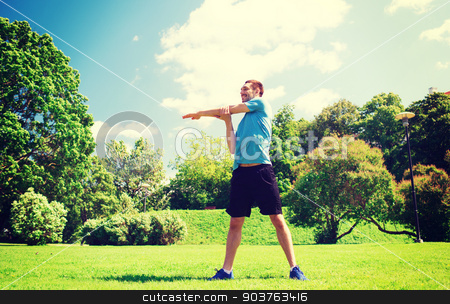 smiling man stretching outdoors stock photo, fitness, sport, training and lifestyle concept - smiling man stretching hand outdoors by Syda Productions