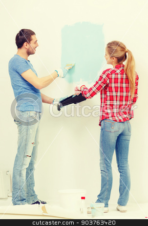 smiling couple painting wall at home stock photo, repair, building and home concept - smiling couple painting wall at home by Syda Productions
