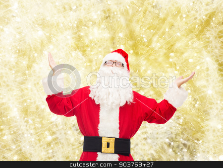 man in costume of santa claus stock photo, christmas, holidays and people concept - man in costume of santa claus with raised hands over yellow lights background by Syda Productions