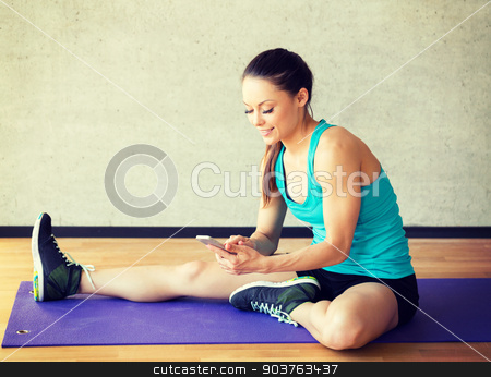 smiling woman stretching leg on mat in gym stock photo, fitness, sport, training and lifestyle concept - smiling woman stretching leg on mat in gym by Syda Productions