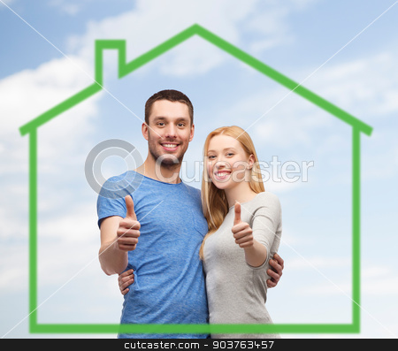smiling couple showing thumbs up over green house stock photo, love, home, people, gesture and family concept - smiling couple hugging and showing thumbs up over green house and blue sky with clouds background by Syda Productions