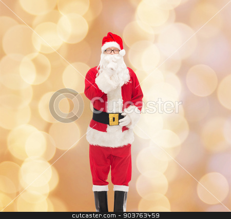 man in costume of santa claus stock photo, christmas, holidays and people concept - man in costume of santa claus making hush gesture over beige lights background by Syda Productions