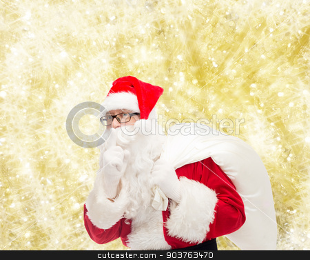 man in costume of santa claus with bag stock photo, christmas, holidays and people concept - man in costume of santa claus with bag making hush gesture over yellow lights background by Syda Productions