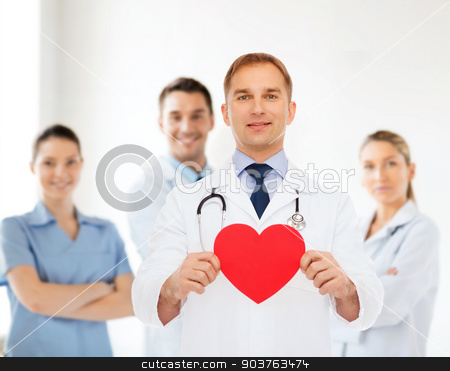 smiling male doctor with red heart and stethoscope stock photo, medicine, profession, charity and healthcare concept - smiling male doctor with red heart and stethoscope over group of medics by Syda Productions