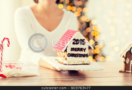 close up of woman showing gingerbread house stock photo, cooking, people, christmas and baking concept - close up of happy woman holding and showing gingerbread house at home by Syda Productions