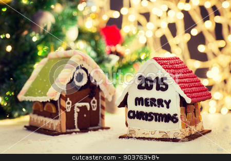closeup of beautiful gingerbread houses at home stock photo, holidays, christmas, baking and sweets concept - closeup of beautiful gingerbread houses on table over lights background by Syda Productions