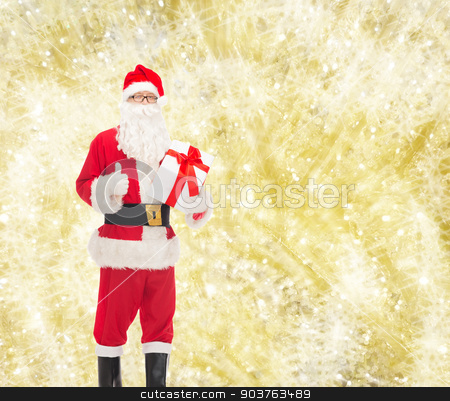 man in costume of santa claus with gift box stock photo, christmas, holidays and people concept - man in costume of santa claus with gift box showing thumbs up gesture over yellow lights background by Syda Productions
