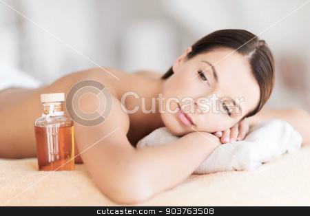 happy woman in spa salon stock photo, beauty and spa concept - happy woman in spa salon lying on the massage desk by Syda Productions