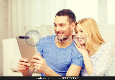 smiling happy couple with tablet pc at home stock photo, love, family, technology, internet and happiness concept - smiling happy couple witl tablet pc computer sitting on the floor at home by Syda Productions