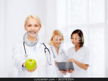 smiling female doctor with green apple stock photo, healthcare and medicine concept - smiling female doctor with stethoscope and green apple by Syda Productions