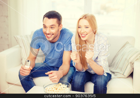 smiling couple with popcorn cheering sports team stock photo, food, love, family, sports, entertainment and happiness concept - smiling couple with popcorn cheering sports team at home by Syda Productions
