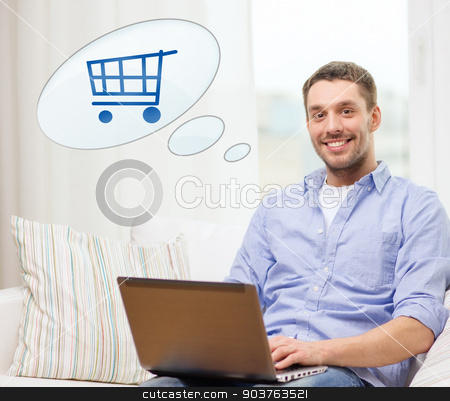 smiling man with laptop shopping online at home stock photo, people, leisure and technology concept - smiling young man with laptop computer and trolley icon shopping online at home by Syda Productions
