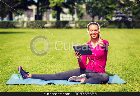 smiling woman with tablet pc outdoors stock photo, fitness, park, technology and sport concept - smiling african american woman with tablet pc and headphones showing thumbs up outdoors by Syda Productions
