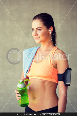 woman with bottle of water in gym stock photo, fitness, sport, training, drink and lifestyle concept - woman with bottle of water in gym by Syda Productions