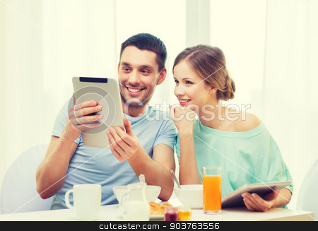smiling couple with tablet pc reading news stock photo, food, home, couple and technology concept - smiling couple with tablet pc reading news and having breakfast at home by Syda Productions