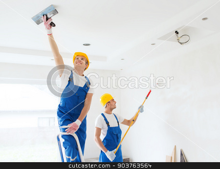 group of builders with tools indoors stock photo, business, building, teamwork and people concept - group of builders in hardhats with plastering tools indoors by Syda Productions
