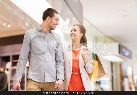 happy young couple with shopping bags in mall stock photo, sale, consumerism and people concept - happy young couple with shopping bags walking and talking in mall by Syda Productions